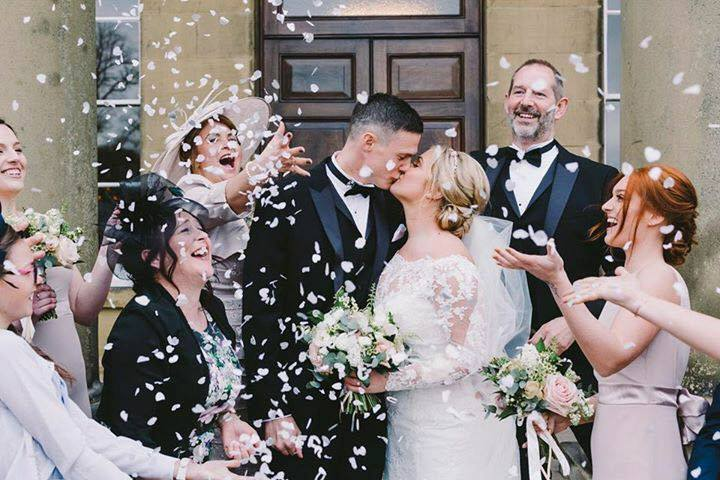 Wedding outdoors confetti kissing bride and groom
